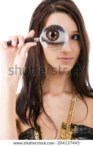 Beautiful brunette studies world through magnifying glass and is surprised. - stock photo