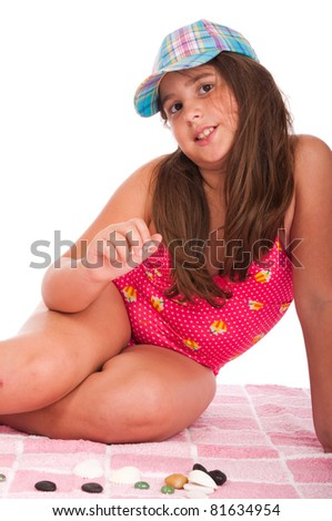 beautiful brunette teenage girl in swimsuit at the beach playing with little stones (studio setting with towel and pebbles, isolated on white background) - stock photo