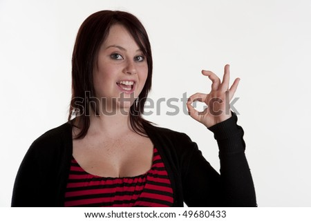 beautiful brunette teenage girl making OK sign with hand white background - stock photo