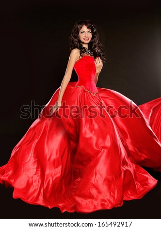 Beautiful brunette wearing in blowing red dress isolated on black background - stock photo