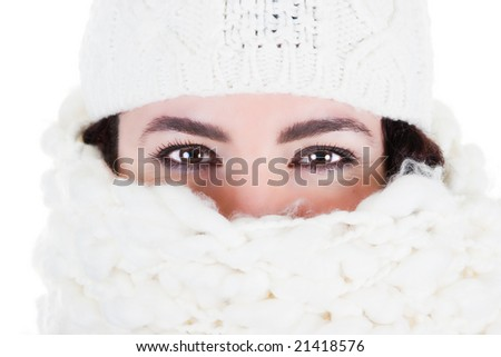 Beautiful brunette with a wool scarf and cap. Close up. Studio shot. - stock photo