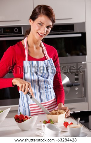 Beautiful brunette with big smile cutting the cake on the kitchen counter - stock photo