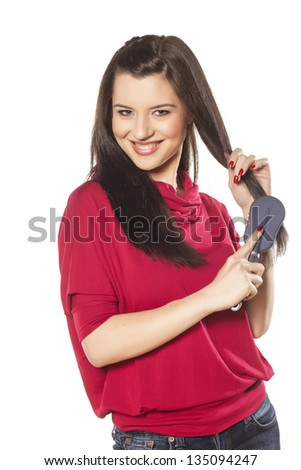 beautiful brunette with blue eyes in a red blouse comb her hair - stock photo