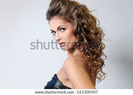 Beautiful brunette with curly hair and in a dress is posing over a light background - stock photo