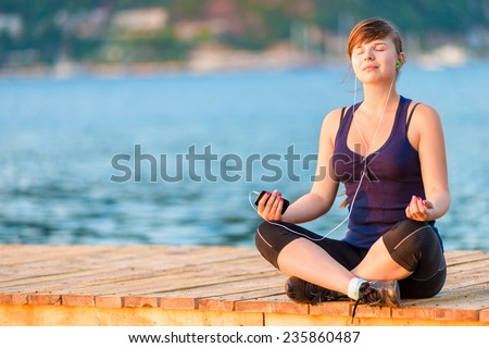 beautiful brunette with eyes closed listening to the player on the pier - stock photo