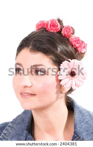 Beautiful brunette with flowers in her hair and a daisy behind her ear - stock photo