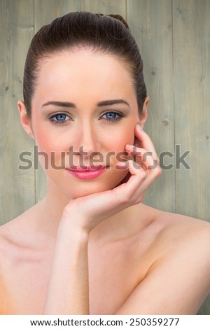 Beautiful brunette with hand on face against bleached wooden planks background - stock photo