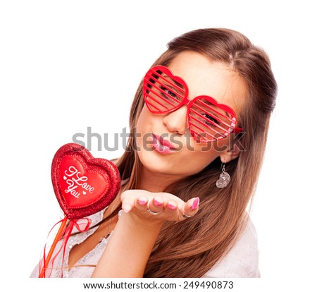 Beautiful brunette with heart shape glasses holding heart and sending kisses, on white background - stock photo