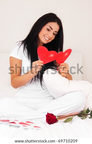 beautiful brunette woman at home was a gift from a loved one, jewelry, postcard, heart and roses. feast day of St. Valentine - stock photo