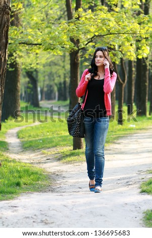 Beautiful brunette woman calling on the phone walking outdoor in the park - stock photo