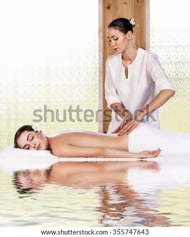 Beautiful brunette woman enjoying a back massage at the health spa - stock photo