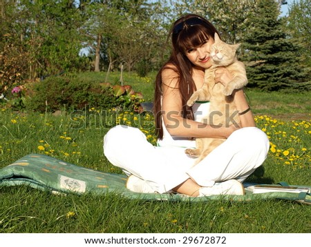 Beautiful brunette woman holding her pet cat. - stock photo