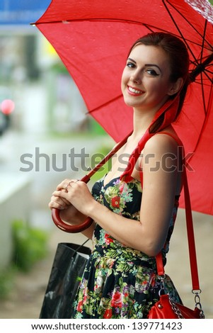 Beautiful brunette woman holding red umbrella out in the rain - stock photo