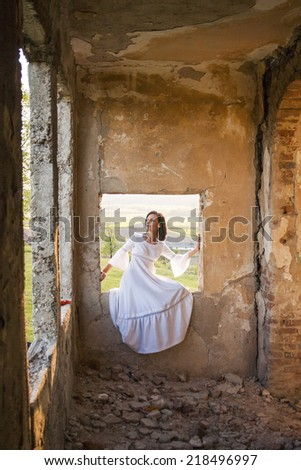 Beautiful, brunette woman in an old, abandoned house, wearing a wedding dress, posing with sunset light. Photo has grain texture visible on its maximum size. Artistic photography  - stock photo