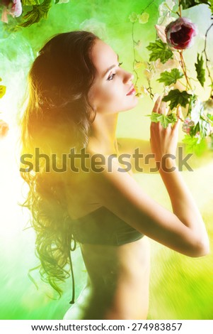 Beautiful brunette woman in bikini among tropical plants. Beauty, fashion. Spa, healthcare. Tropical vacation. - stock photo