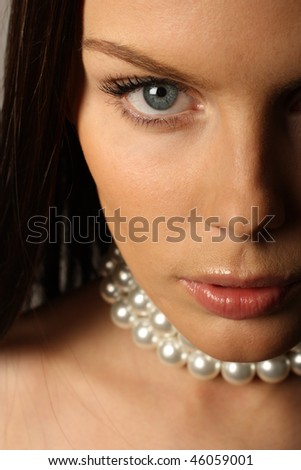 Beautiful brunette woman in pearl beads - stock photo