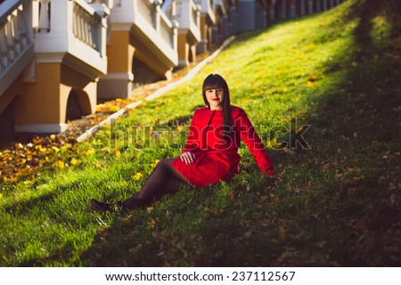 Beautiful brunette woman in red jacket sitting on grass at autumn forest - stock photo