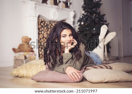 Beautiful brunette woman in shorts and sweater in new year decorated interior with christmas tree in it. Indoors. copy space - stock photo