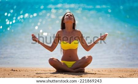 beautiful  brunette woman in yellow bikini posing  meditation yoga in tropical  blue sea water bali has sports and tan body - stock photo