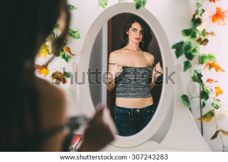 Beautiful brunette woman looking in the mirror while taking off her shirt - stock photo