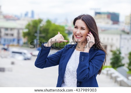 Beautiful brunette woman making a call me gesture, summer outdoors - stock photo