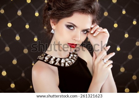 Beautiful brunette woman model with makeup and hairstyle in fashion jewels over bokeh lights background. Elegant lady. - stock photo