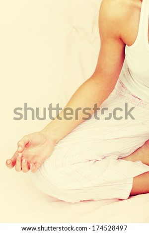 Beautiful brunette woman on bed practicing yoga  - stock photo