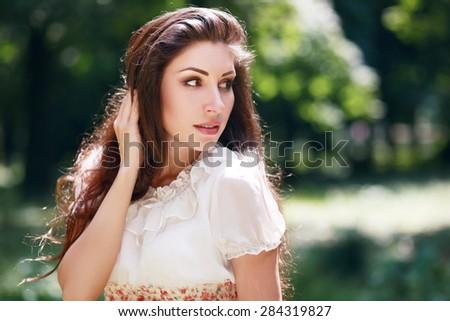 beautiful brunette woman outdoor looking to copyspace - stock photo