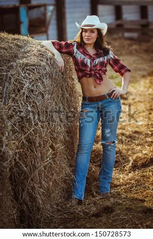 beautiful brunette woman posing on farmland - stock photo