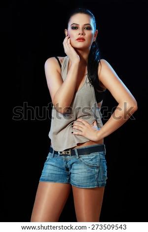 beautiful brunette woman posing over black background - stock photo
