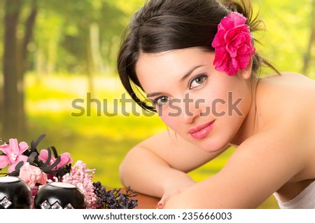 beautiful brunette woman relaxing lying down in outdoor spa - stock photo