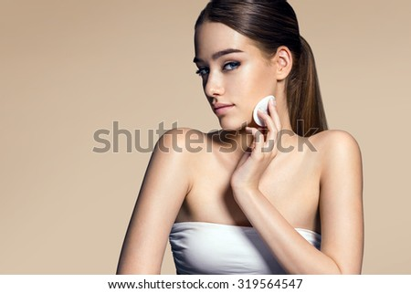 Beautiful brunette woman removing makeup from her face, skin care concept / photo composition of brunette girl with beige background - stock photo