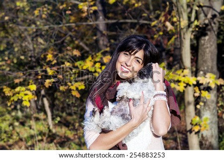 beautiful brunette woman smiling and hugging her little cute white dog in the autumn park - stock photo