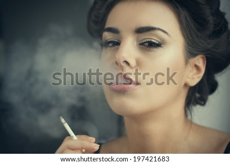 beautiful brunette woman smokes at home  - stock photo