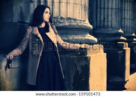 Beautiful brunette woman standing on the city street. - stock photo