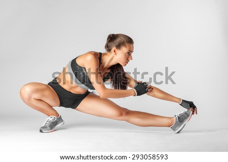 beautiful brunette woman stretching her legs, warm up isolated on white background - stock photo