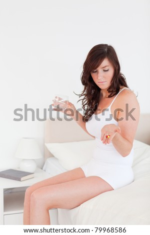 Beautiful brunette woman taking some pills while sitting on a bed - stock photo