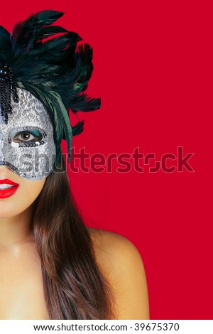 Beautiful brunette woman wearing a masquerade mask against a red background. - stock photo
