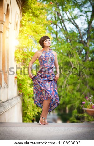 beautiful brunette woman wearing bright dress posing in autumn park. attractive slim caucasian sexy girl with brown hair outdoor. Alluring lady with short hairstyle and professional makeup. series - stock photo