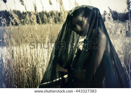 Beautiful brunette woman wearing long black dress and black veil posing among the reeds. The old times, the Gothic style. Fashion. - stock photo