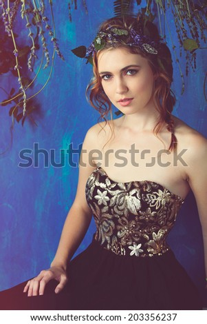 Beautiful brunette woman with braid hairstyle and natural makeup. Wearing black bohemian sequin corset dress. Against blue grunge background. Wearing flowers in her hairstyle  - stock photo