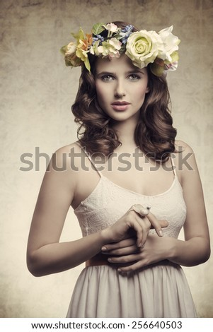 Beautiful, brunette woman with colorful makeup, wreath of flowers on head, little bird on her finger. - stock photo