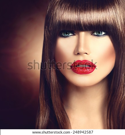 Beautiful brunette woman with fashion fringe haircut and professional makeup. Red lips, smooth brown hair - stock photo