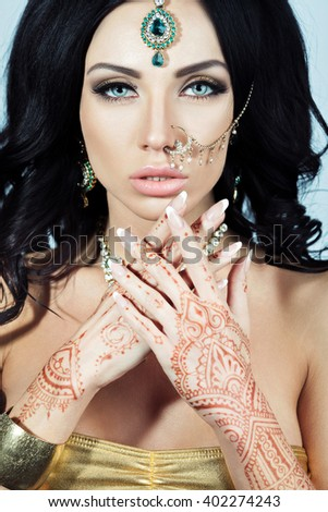 Beautiful Brunette Woman With Indian Jewelry Glamour Style. Curly Hairstyle. Bright Makeup. Sexy Lips - stock photo