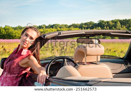 Beautiful brunette woman with long hair near car - stock photo