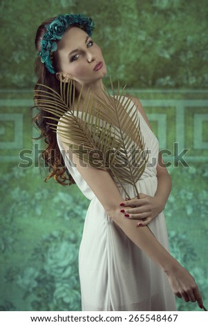 beautiful brunette woman with long wavy hair and white dress posing in spring shoot with floral crown and palm leafs in the hands. Sensual expression looking in camera  - stock photo
