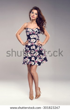 Beautiful brunette woman with lovely long hair posing in a sexy summer  dress in a studio. Fashion photo - stock photo