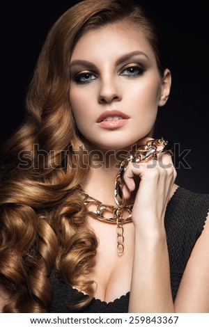 Beautiful brunette woman with perfect skin, bright makeup and gold jewelry. Beauty face. Picture taken in the studio on a grey background - stock photo