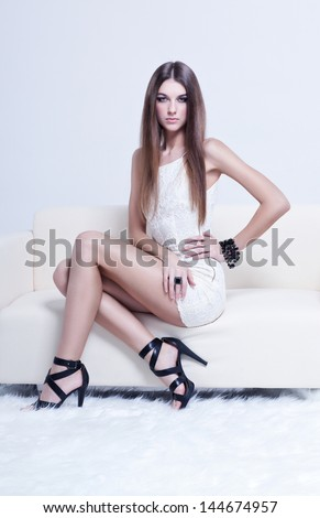 beautiful brunette young woman in white dress and black shoes sitting on couch - stock photo
