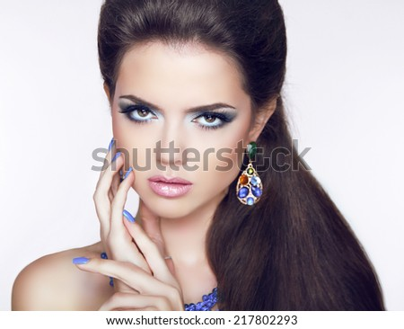 Beautiful Brunette young woman with fashion earring. Makeup. Manicured nails. Long hair. - stock photo